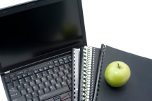 Study concept closeup of an open laptop, with workbooks and notebooks and a fresh green apple